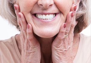 Senior woman smiling after receiving her dentures at Sylvan Heights Dental in Portland, OR